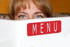 La belle fille juge le menu disponible Photo stock