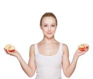 La belle fille la blonde tient des moitiés de pomme Images stock
