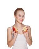La belle fille la blonde tient des moitiés des pommes Photographie stock