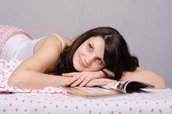 La belle fille lisant un magazine rêve photographie stock libre de droits