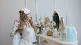 La belle fille lisse devant le miroir dans des pyjamas le matin banque de vidéos