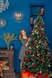 La belle fille même se tient près de l'arbre de Noël et des jouets de contacts photographie stock libre de droits