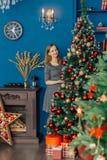 La belle fille même se tient près de l'arbre de Noël et des jouets de contacts photo stock