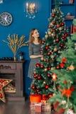 La belle fille même se tient près de l'arbre de Noël et des jouets de contacts images stock