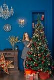 La belle fille même se tient près de l'arbre de Noël et des jouets de contacts photos libres de droits