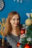 La belle fille même se tient près de l'arbre de Noël et des jouets de contacts image libre de droits