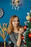 La belle fille même se tient près de l'arbre de Noël et des jouets de contacts images libres de droits