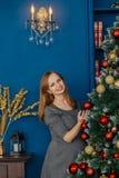 La belle fille même se tient près de l'arbre de Noël et des jouets de contacts photographie stock