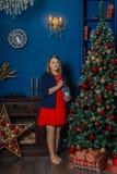 La belle fille même se tient près de l'arbre de Noël et des jouets de contacts photo libre de droits