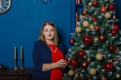 La belle fille même se tient près de l'arbre de Noël et des jouets de contacts image stock