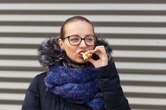 La belle fille mange ardemment un hamburger sur la rue image libre de droits