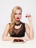 La belle fille mange la cerise Photographie stock libre de droits