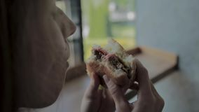 La belle fille mange un hamburger Restaurant d'aliments de pr?paration rapide banque de vidéos