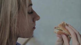 La belle fille mange un hamburger Restaurant d'aliments de pr?paration rapide clips vidéos
