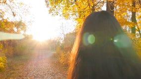 La belle fille marche au soleil lumineux de forêt d'automne Coucher du soleil dans le plan rapproché de forêt Mouvement lent clips vidéos