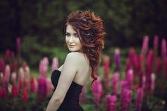 La belle fille mignonne de brune dans la robe noire, près du buisson fleurit avec les fleurs roses Photo libre de droits
