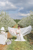 La belle fille mignonne sexy dans une robe blanche légère dans le jardin de floraison de pomme voit sur l'hamac avec un livre Photo libre de droits