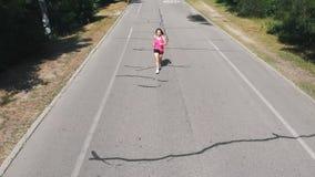La belle fille mince dans la chemise rose pratique sa course Jeune femme de brune dans des écouteurs faisant des exercices dans l banque de vidéos