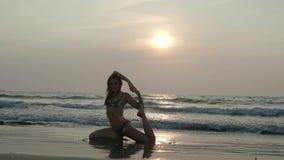 La belle fille mince dans un maillot de bain est engagée dans le yoga sur la plage au coucher du soleil 4K clips vidéos