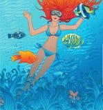 La belle fille nage avec les poissons tropicaux Image stock