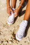 La belle fille noire adolescente dans des espadrilles blanches sur le sable de soit Photos stock