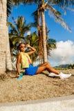 La belle fille noire adolescente dans la jupe bleue s'asseyent avec son lo de penny Image libre de droits