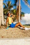 La belle fille noire adolescente dans la jupe bleue s'asseyent avec son lo de penny Images libres de droits