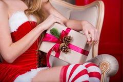 La belle fille portant le père noël vêtx avec le cadeau de Noël à disposition Concept de Noël Photo stock