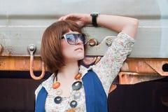 La belle fille près d'un véhicule ferroviaire rouillé Photographie stock