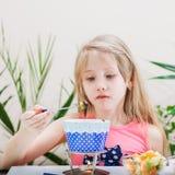 La belle fille prépare la fondue de chocolat avec des kiwis Image stock