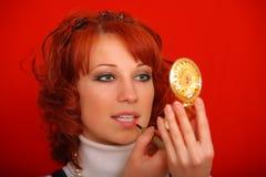 La belle fille regarde dans le miroir et le rouge à lèvres Image stock