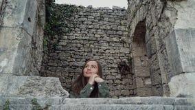 La belle fille regarde la fenêtre d'un château antique comme une princesse dans un plan rapproché clips vidéos