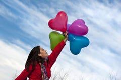 La belle fille retenant le coeur monte en ballon sur le fond bleu image stock