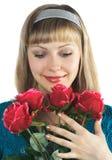 La belle fille retient le bouquet des roses rouges Image stock