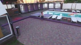 La belle fille s'asseyant sur un canapé près de la piscine invite le bourdon à elle La fille avec des gestes règle le vol de banque de vidéos