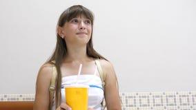 La belle fille s'assied à la table dans le café, le cocktail potable et le sourire clips vidéos