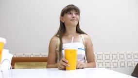La belle fille s'assied à la table dans le café, le cocktail potable et le sourire banque de vidéos