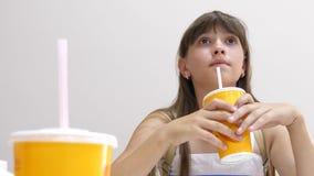 La belle fille s'assied à la table en café et cocktail potable Plan rapproché banque de vidéos