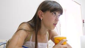 La belle fille s'assied à la table en café et cocktail potable et sourire clips vidéos