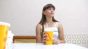 La belle fille s'assied à la table en café et cocktail potable et sourire banque de vidéos