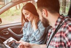 La belle fille s'assied avec son ami dans la voiture et regarde l'écran Elle tient la main sur son cou avec des yeux Photo stock