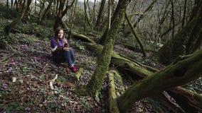 La belle fille s'assied dans la forêt de conte de fées et regarde la fleur dans sa main banque de vidéos