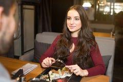 La belle fille s'assied devant son ami et le regarde Elle est des salades tout préparées qu'ils ont commandées Image libre de droits