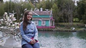 La belle fille s'assied sur un fond d'une maison multicolore d'oiseau sur l'étang Les mouettes volent à partir du toit du banque de vidéos