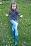 La belle fille s'assied sur une herbe verte Photographie stock