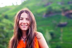La belle fille sans maquillage avec de longs cheveux sourit dans la perspective des montagnes Photos stock