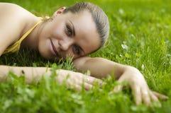 La belle fille se repose sur l'herbe et sourit Photographie stock libre de droits