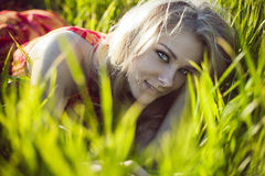 La belle fille se situe dans une herbe verte photo stock