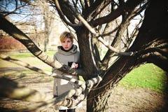 La belle fille se tient près de l'arbre branchu au printemps Photos libres de droits