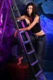 La belle fille se tient près des escaliers dans des jeans et d'un dessus sur le treillis Photo stock